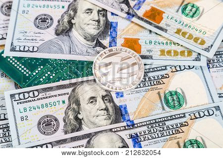 Silver litecoin lying over american dollar bills and electronic circuit board. Business concept
