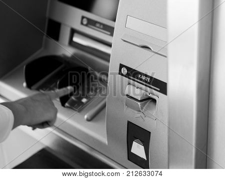 PIN security - side view of woman using ATM Automatic Teller Machine cash machine to enter the security PIN and retrieve withdrawal withdrawal money