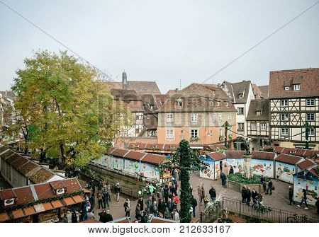COLMAR FRANCE - NOV 23 2015: Aerial view of Colmar Alsace Christmas market with chalets market stall selling gifts toys food and people admiring
