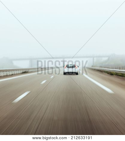FRANKFURT GERMANY - NOV 23 2017: Rear view of white car driving on German autobahn undern bridge - fast motion in safety condition during heavy mist