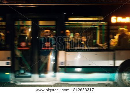 Silhouettes commuting in bus people men women and kids commuting home office and city at night - bus in motion