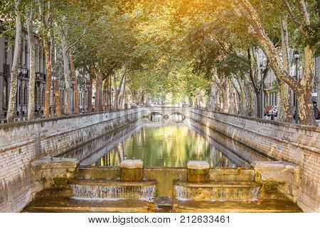 View on the beautiful water channel during the sunny day in Nimes city in the Occitanie region of southern France