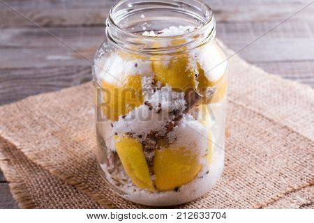 Preserved lemons with salt on a wooden board in a jar
