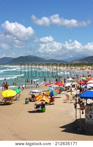 JOAQUINA BEACH, FLORIANOPOLIS, SANTA CATARINA, BRAZIL - MARCH 22, 2009: Many colorfull sunshades at the beach. People relaxing and enjoying the sun and the sea. The hills in the background.