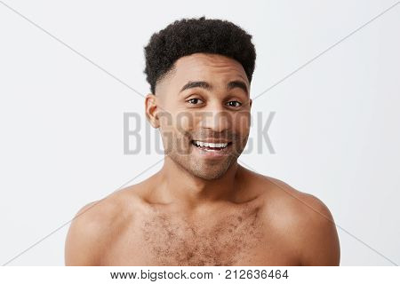 Close up of young good-looking attractive cheerful black-skinned man with afro hairstyle with naked torso smiling with teeth, looking in camera with happy an relaxed expression. Health and beauty.