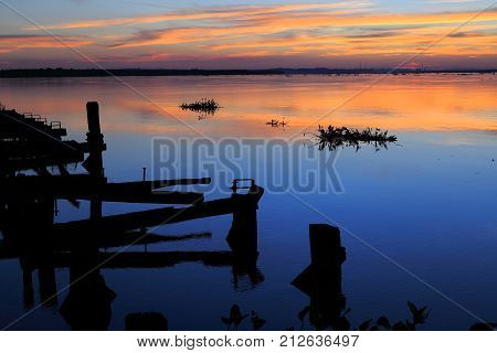 Beautiful sunset on the river parana in entre rios, Argentina, south america. An old wooden pier, the sky in orange tones is reflected on the water and aquatic plants pass by the river.