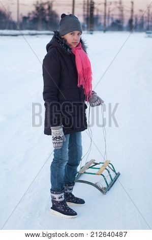 A teenage girl in the winter with sledges in the snow.