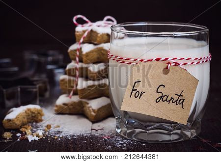 Cookies for Santa with glass of milk with tag for Santa and christmas tree made with star cookie cutter gingerbread new year pasrty decorated with rope bow on wooden table. Festive sweet pastry