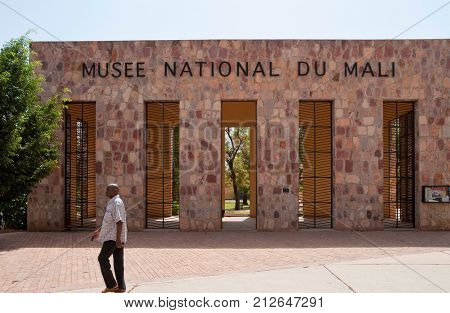 BAMAKO, MALI - CIRCA FEBRUARY 2012: A man walks past the Mali National Museum entrance gate.