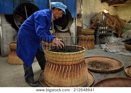 HUANGSHAN, ANHUI PROVINCE, CHINA - CIRCA OCTOBER 2017: A man inside the tea factory in the process of making tea.