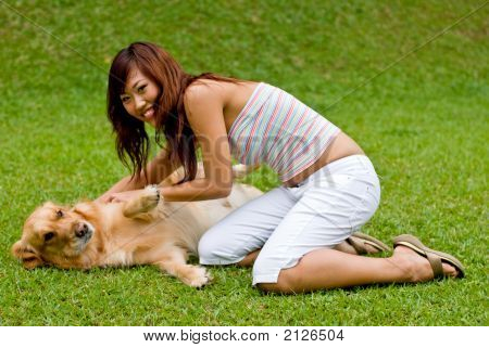 A pretty asian women in garden with a dog poster