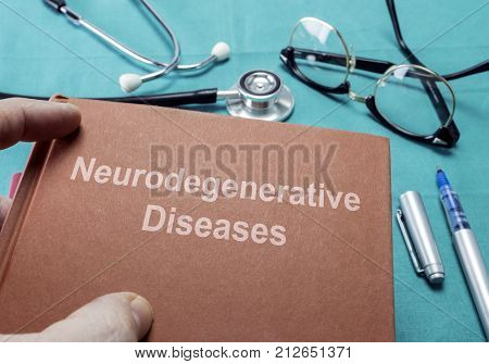 Doctor Holds Book On Neurodegenerative Diseases In A Hospital