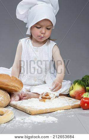 Cooking Ideas and Concepts. Portrait of Little Caucasian Girl in Cook Hat and Lips in Flour Sitting in Front of Fresh Buns. Sieving Powder on Pastry. Against Gray. Vertical Image