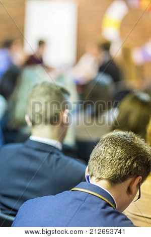 Round Table Discussion and Presentations.People Listening to the Group Of Young Businessmen Having a Talk At the round Table on Stage.Vertical Image