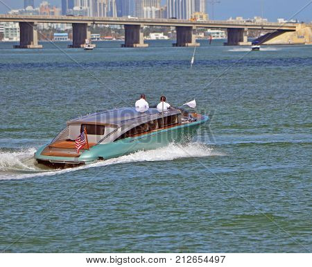 Ultra luxury motor launch speeding on the florida intra-coastal waterway off Miami Beach with a Julia Tuttle Causeway bridge in the background.