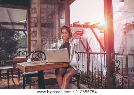 Beautiful girl working on her laptop in caffe.