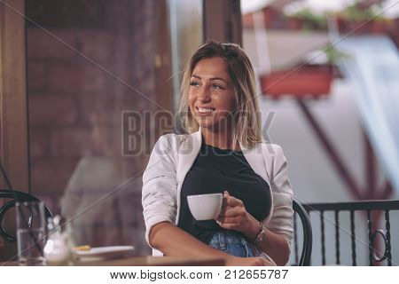 Beautiful young women sitting in caffe and drinking coffee.