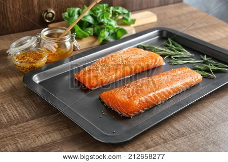 Baking sheet with salmon fillet in honey mustard marinade on table