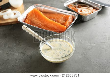 Bowl with lemon mustard marinade for salmon on table