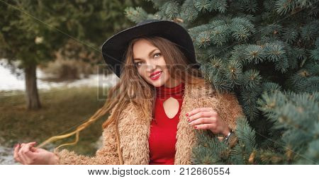 Young attractive girl outdoors in winter. She is dressed in a wide-brimmed hat and fur coat. The girl is standing next to the fir-tree.