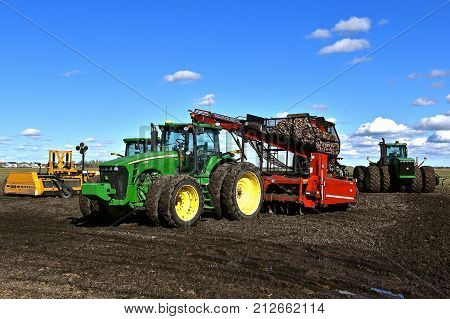 MOORHEAD, MINNESOTA, October 2, 2017: The John Deere 8430 tractor pulling a beet picker is a product of John Deere Co, an American corporation that manufactures agricultural, construction, forestry machinery, diesel engines, and drivetrains.