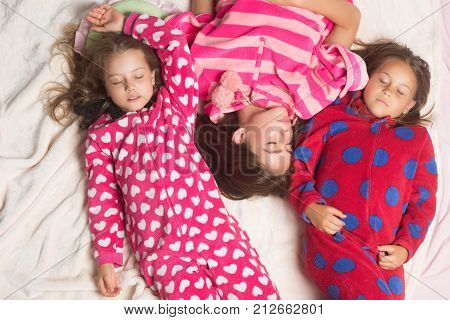 Sisters or friends in pajamas sleep in bed top view. Good night napping bedtime slumber dream sleepover concept