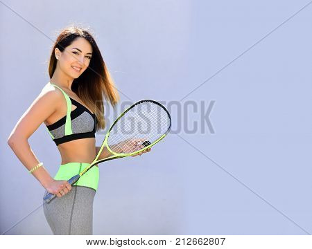 Woman in sportswear with squash racket on grey background. Girl athlete with sport bat with happy face. Sport and success. Health and fitness. Dieting and sport game copy space