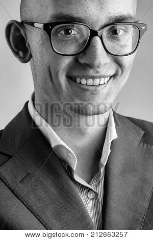 young fashion businessman with nerd glasses on smiling face and stylish hairdo in jacket posing on grey background