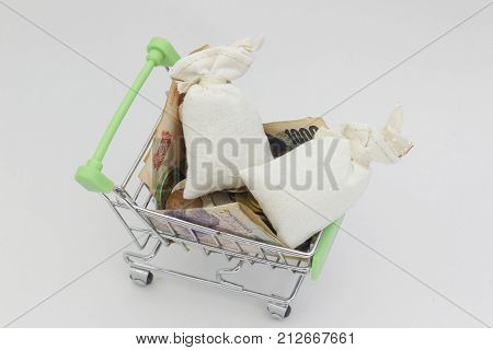 Trolley filled with coins money and two gunny bags on isolated white background. Gunny bag is symbolic.