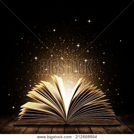 Open book on wooden vintage table with mystic magic bright light on background