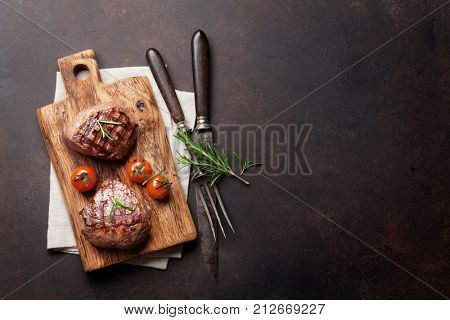 Grilled fillet steak on stone table. Top view with space for your text