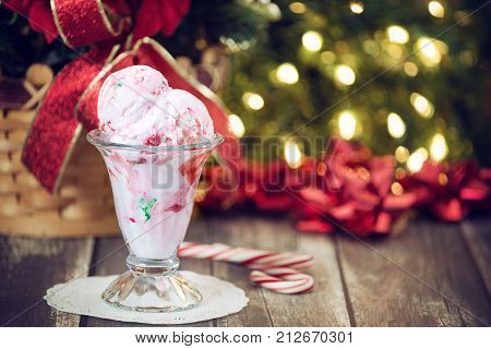 Peppermint ice cream served in a glass bowl. Displayed with candy canes on wooden rustic table. Sparkling Christmas tree lights background.