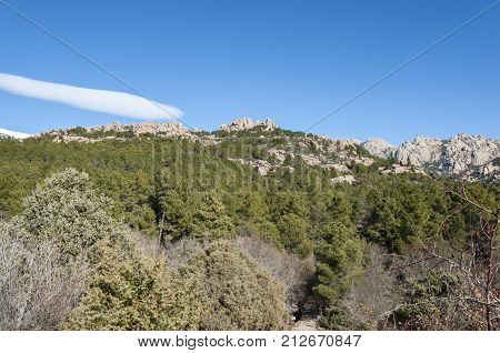 Views of La Pedriza from Canto Cochino, in Guadarrama Mountains National Park, Madrid, Spain. In the background can be seen The Cancho de los Muertos (Peak of the deads) El Pajaro (Bird Peak) and Las Buitreras (Vulture Peak)
