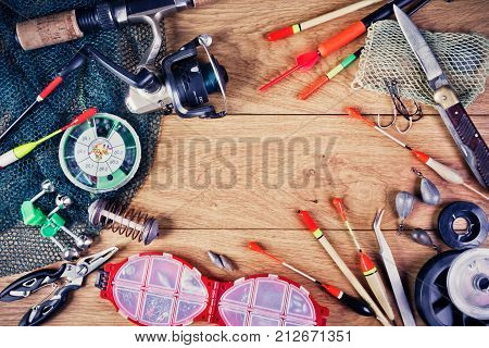 Fishing tackle - fishing hooks fishing line and floats fishing rod with a reel net knife and other tools on a wooden background. Still life. View from above.