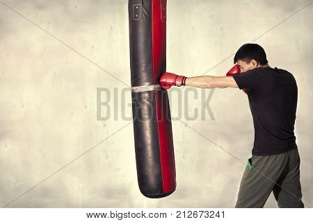Man boxing hit punching bag. Isolated background. Young