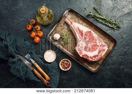 Raw tomahawk beef steak with ingredients for grilling: seasoning, fresh rosemary and olive oil on black background, top view