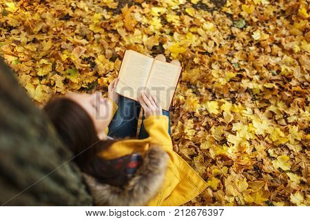 A Beautiful Happy Smiling Brown-haired Woman In Yellow Coat And Jeans Sitting Under The Maple Tree W