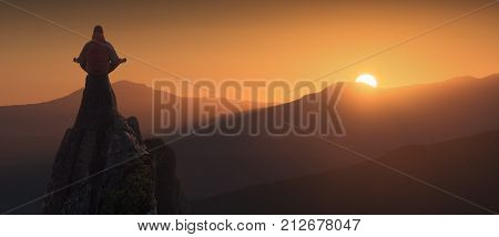 Silhouette of human who meditating in sitting yoga position on the top of mountain in a light of rising sun. Zen meditation peace