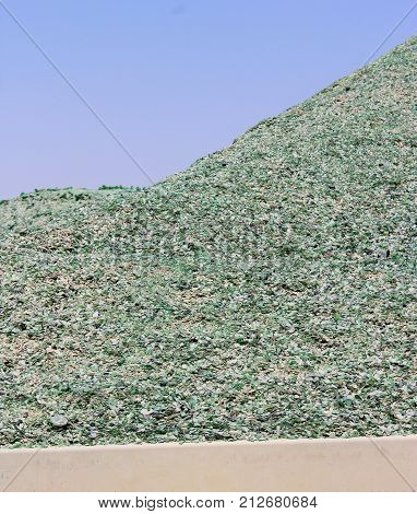 A Mountain Of Small Fragments Of Green Glass From Broken Bottles For Recycling Near A Glass Bottles