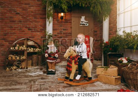 Playful Happy Cute Little Child Boy Dressed In Pajamas Sitting On Rocking Horse In Decorated New Yea