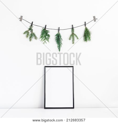 Christmas composition. Black frame and christmas tree branches on white background. Front view mock up copy space square