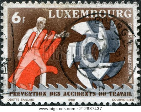 LUXEMBOURG - CIRCA 1980: A stamp printed in Luxembourg is dedicated to 9th World Congress on Prevention of Occupational Accidents & Diseases Amsterdam shows a Man hand gears circa 1980