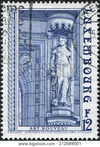 LUXEMBOURG - CIRCA 1980: A stamp printed in Luxembourg Goddess of Fertility - Ceres by Jean Mich a sculpture in front of the main entrance to the State Savings Bank circa 1980