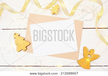 Christmas mail on a white wooden background with a golden angel and christmas tree. Flat lay top view photo mockup.