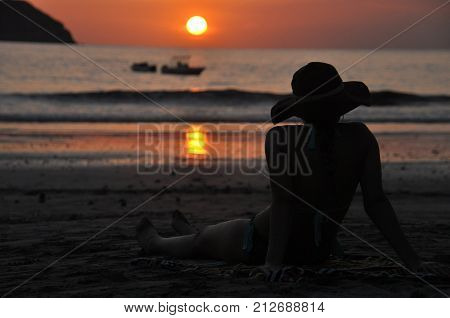 Girls in swimsuits sitting on the beach in Costa Rica and admiring the sunset