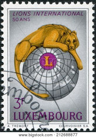 LUXEMBOURG - CIRCA 1967: A stamp printed in Luxembourg is dedicated to the 50th anniversary of Lions Clubs International shows Lion Globe and Lions Emblem circa 1967