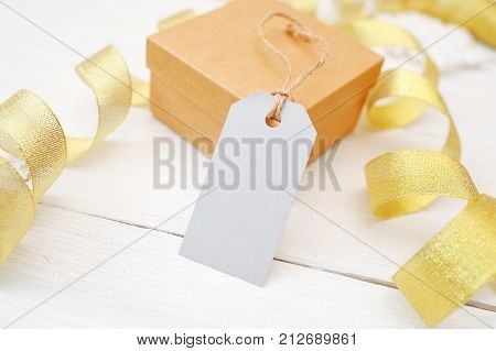 mockup christmas gift with blank tag on white wooden background with gold ribbon.