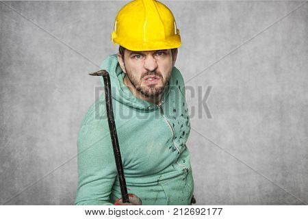 An Angry Worker Holds A Crowbar In His Hand