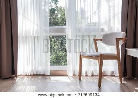 one white woodwn chiar in a relaxing room