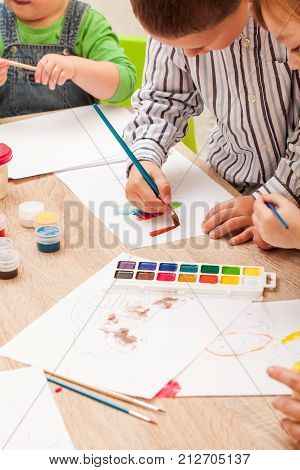 Children learn to paint with a brush and watercolors on paper in the kindergarten